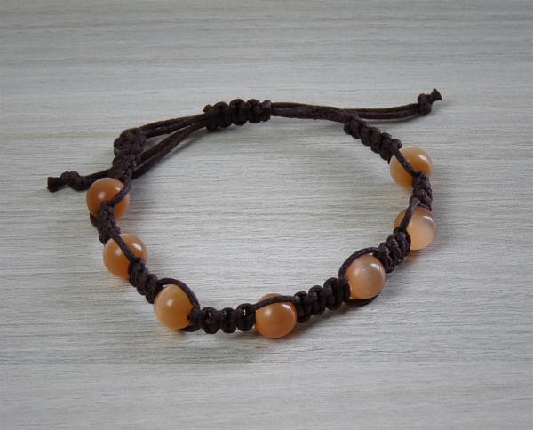 Bracelet marron avec des perles œil de chat oranges